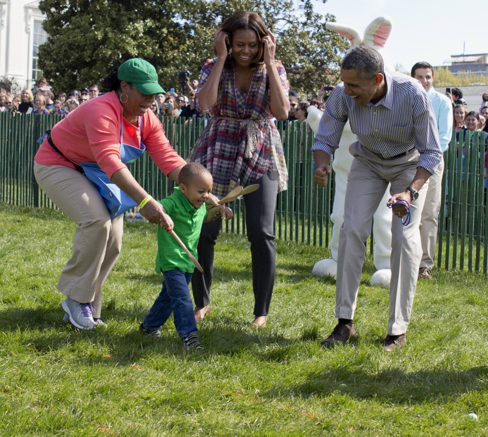 President Obama and first lady Michelle Obama cheer a child as they host the White House Easter Egg Roll on the South Lawn of the White House in Washington on Monday.