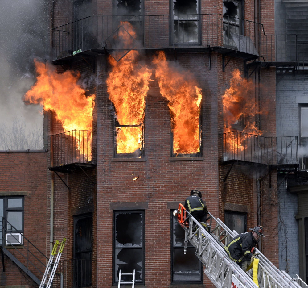 Boston firefighters work a multi-alarm brownstone fire on March 26. Two firefighters died in the wind-driven blaze that ripped through the brownstone.