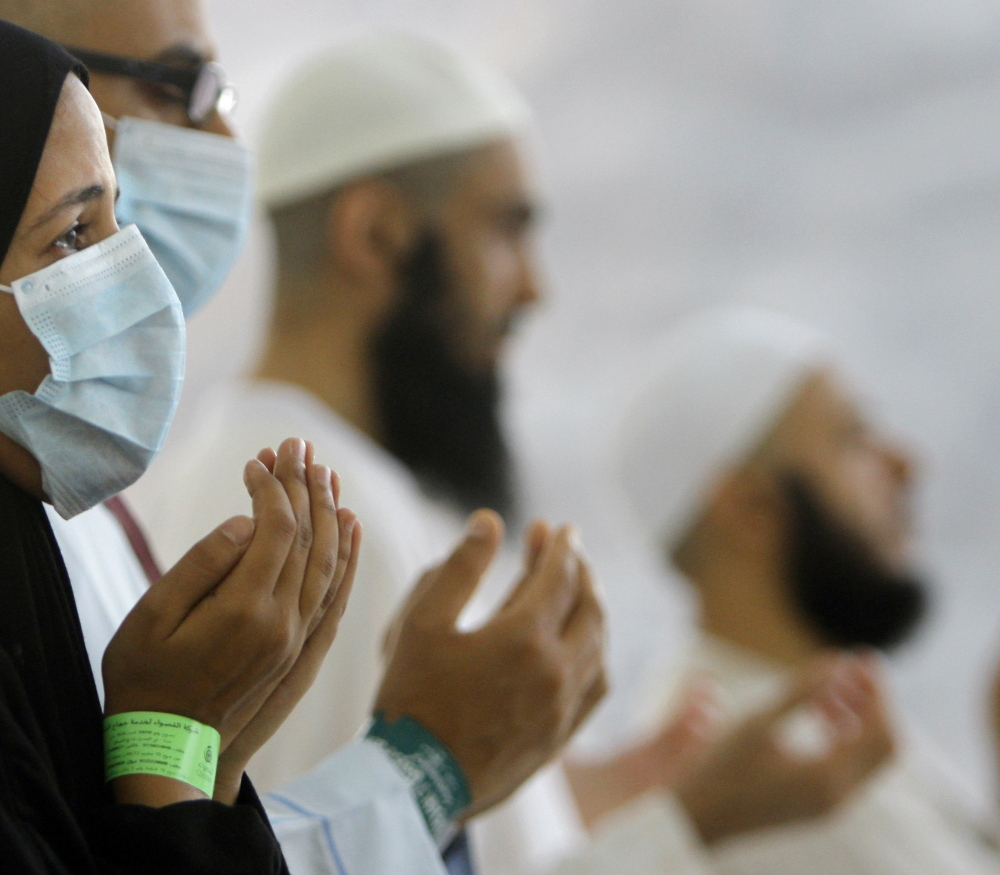 Muslim pilgrims, some wearing masks, pray near Mecca in Saudi Arabia in 2013.