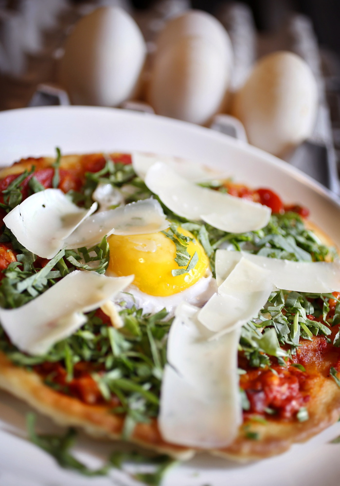 A pizza topped by a fried duck egg prepared by executive chef Pete Sueltenfuss at Grace in Portland.