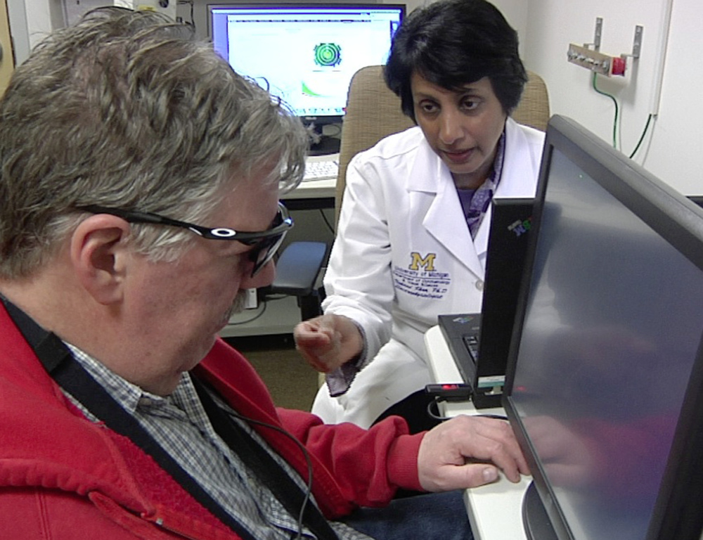 Dr. Naheed Khan, right, works with Roger Pontz, left, on an exercise to test how well he sees shapes on a computer screen at the University of Michigan Kellogg Eye Center, in Ann Arbor.