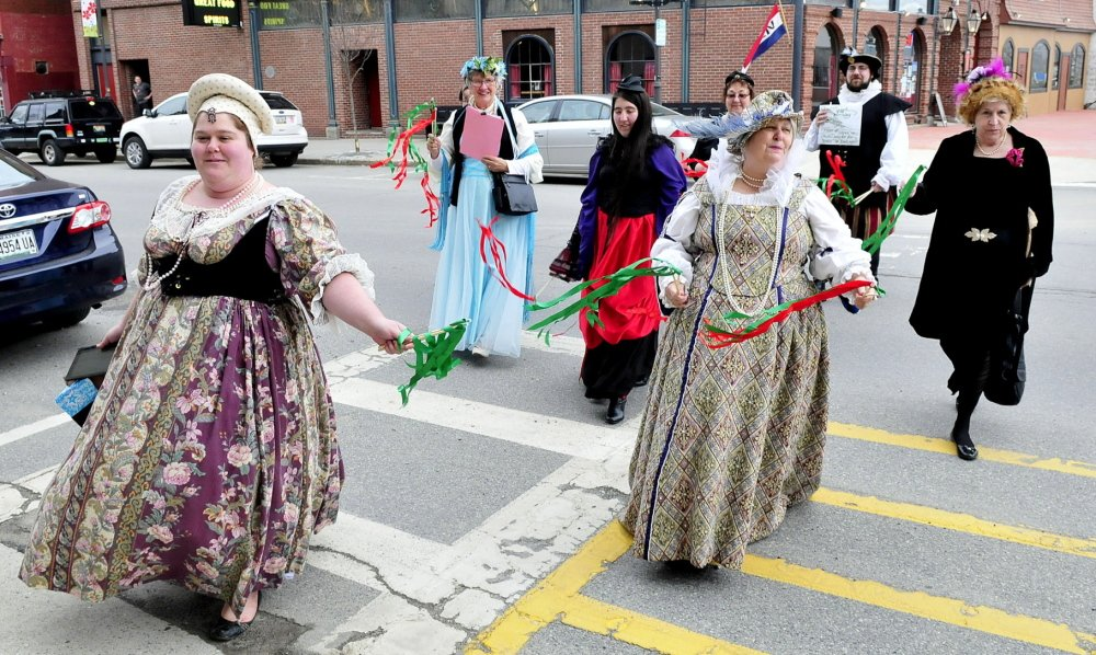 Dressed in period outfits, a group from the Recycled Shakespeare Company crosses Main Street in downtown Waterville on Wednesday during a celebration of William Shakespeare's 450th birthday. Leading the group are Emily Rowden Fournier, left, and her mother, Lyn Rowden, who was dressed as Queen Elizabeth I.