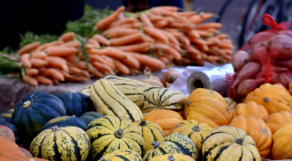 Local foods, like the carrots and squash displayed at the Portland Farmers' Market last fall, could appear on more school lunch menus if legislators override Gov. LePage's veto of a proposal that would let small growers more easily reach buyers like school districts and supermarkets.