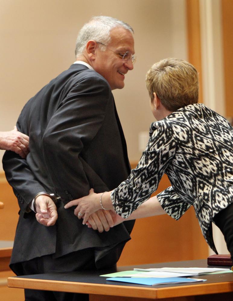 Monsignor Edward Arsenault reaches out with his handcuffed hand to shake hands with prosecutor Jane Young after pleading guilty to three felony theft charges in Hillsborough County Superior Court in Manchester, N.H., on Wednesday.