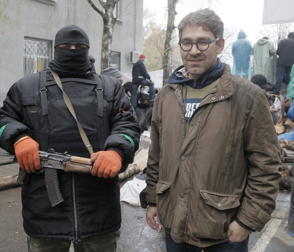 U.S. reporter Simon Ostrovsky stands with a Pro-Russian gunman at a seized police station in the eastern Ukraine town of Slovyansk on April 13. Gunmen admitted Wednesday that they are holding Ostrovsky captive.