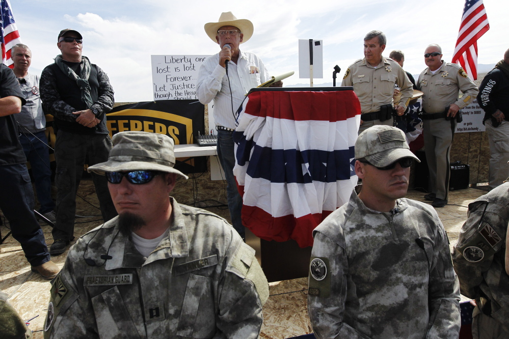 Rancher Cliven Bundy, center, addresses his supporters alongside Clark County Sheriff Doug Gillespie, right, on April 12. Bundy informed the public that the BLM had agreed to cease the roundup of his family's cattle.