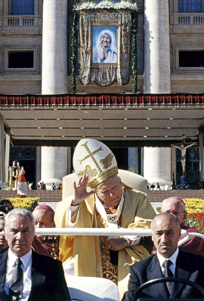 Pope John Paul II in his popemobile waves to the crowd as he leaves St. Peter's Square after the beatification ceremony of Mother Teresa of Calcutta, depicted in a tapestry hung on the Basilica's facade, at the Vatican. John Paul II declared more saints – 482 – than all his predecessors combined, considering them role models for a church desperately in need of them.