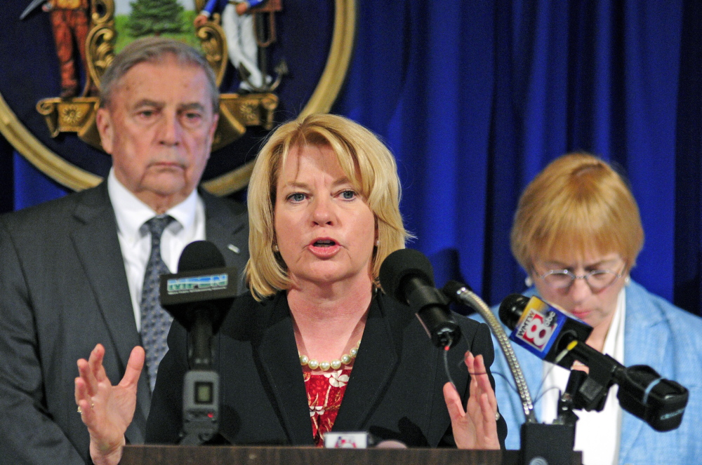 Assistant Attorney General Lisa Marchese, center, speaks during a news conference announcing release of the 10th report of the Domestic Abuse Homicide Review Panel on Thursday in the State House Hall of Flags in Augusta. She is flanked by Department of Public Safety Commissioner John Morris, left, and Attorney General Janet Mills, who also spoke at the event.