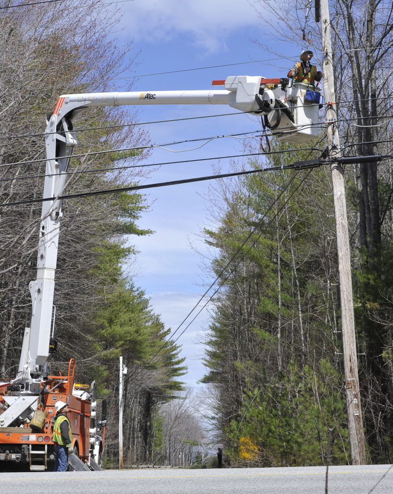 Central Maine Power linemen Shannon Trivett and Tim Laney, in the bucket, repair a downed power line on Maine Avenue in Standish on Thursday.