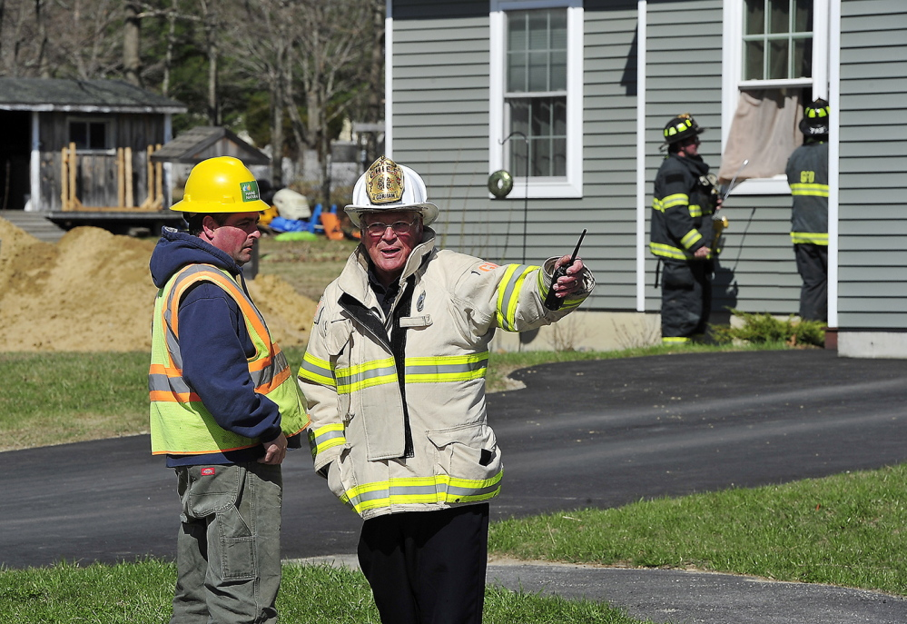 Gorham firefighters open the windows to this unoccupied home as Gorham Fire Chief Robert Lefevre talks with a Maine Natural Gas representative after an excavator being used to build new housing foundations ruptured a gas line main at Hawkes Farm development in Gorham.