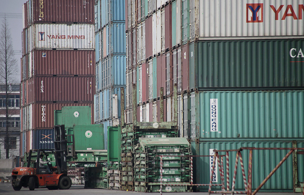A forklift arranges shipping containers near a port in Shanghai in 2011. U.S. manufacturers have grown more competitive over the past decade compared with factories in China, Brazil and most of the world's other major economies.