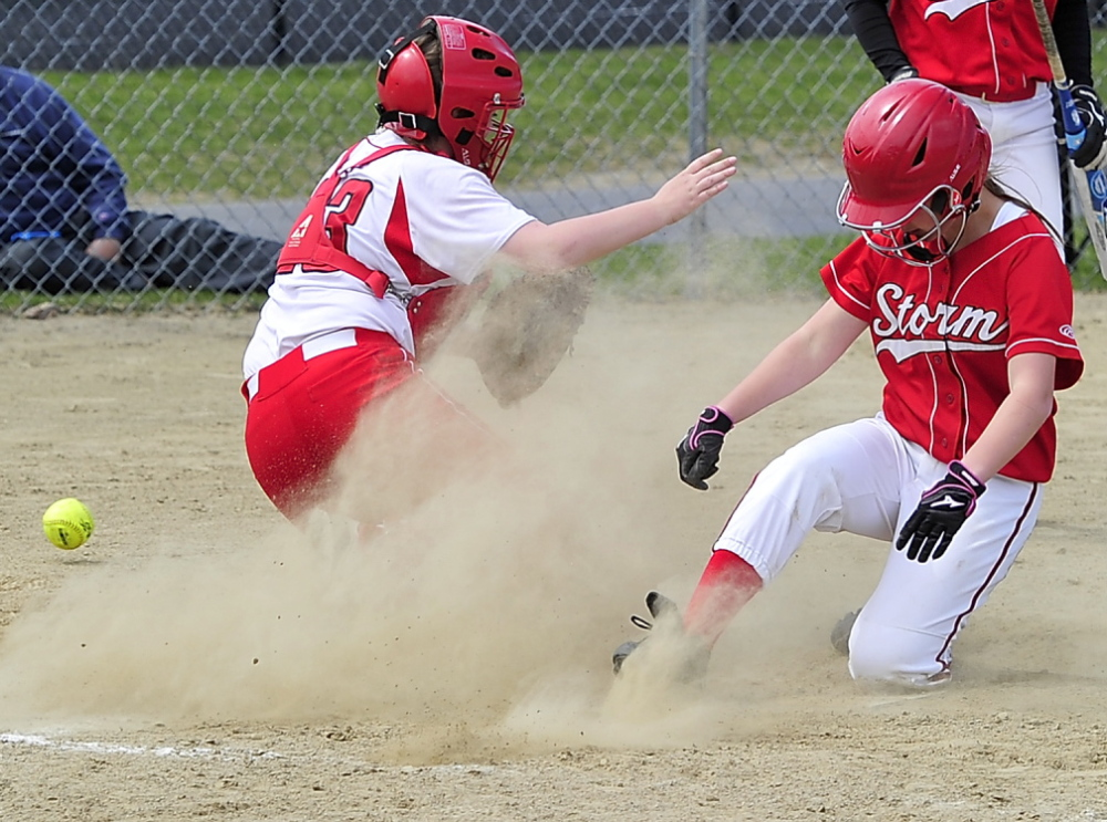 Chloe Gorey of Scarborough slides home safeley as the ball gets past South Portland catcher Kiley Kennedy during Friday's SMAA softball game in Scarborough. Scarborough won, 13-4.