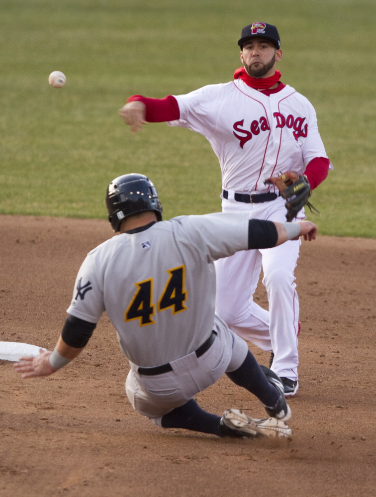 Shortstop Deven Marrero of the Portland Sea Dogs fires to first as Kyle Roller of the Trenton Thunder tries unsuccessfully to break up a double play during Trenton's 14-10 victory at Hadlock Field. The Thunder scored four runs in the ninth inning to pull away from a 10-10 tie.