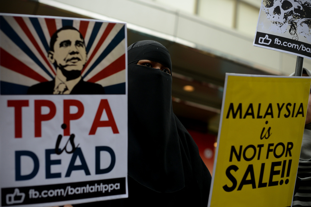 A Muslim woman, in Kuala Lumpur, Malaysia, on Saturday, holds placards during a protest against the Trans-Pacific Partnership in advance of President Obama's visit. The president is taking two tracks in his words about China.
