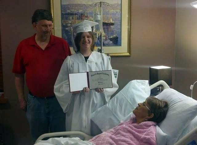 Melissa Shumaker, right, looks on as her 17-year-old daughter Evie Shumaker of Newport, Ohio, displays her diploma after a special high school graduation ceremony in the hospice at Licking Memorial Hospital in Newark, Ohio.