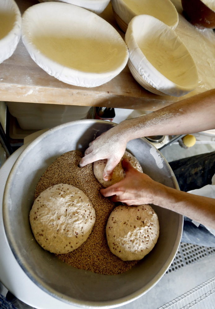 Olins coats dough rounds with seeds. He usually shows up for a Saturday morning market with a half-dozen varieties of breads, classic biscotti and pastries made from croissant dough.