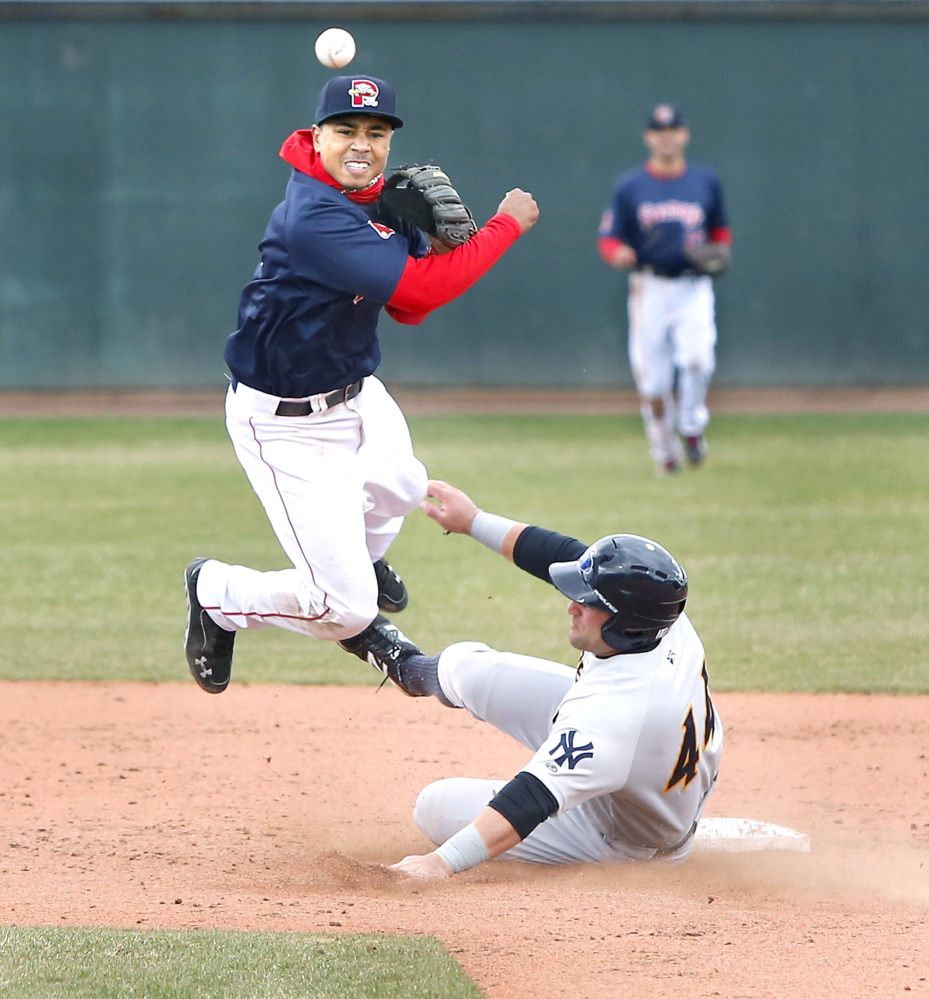 Sea Dogs second baseman Mookie Betts avoids Thunder first baseman Kyle Roller to turn a double play at Hadlock Field in Portland on Sunday.