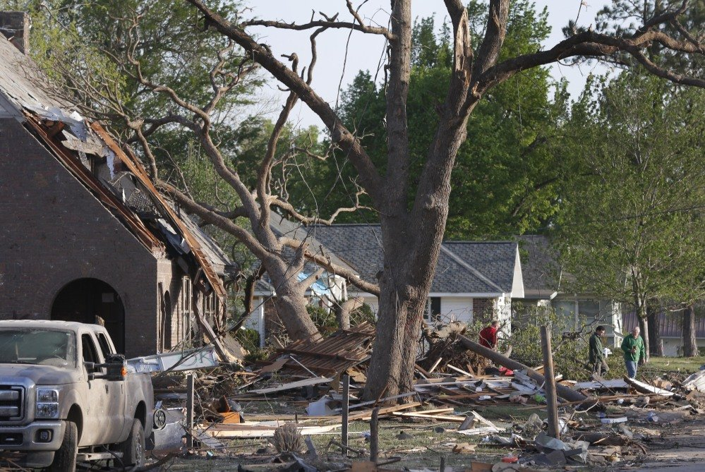 Residents view damage from a Sunday night tornado in Baxter Springs, Kan., Monday. The tornado left a trail of shattered homes, twisted metal and hanging power lines.