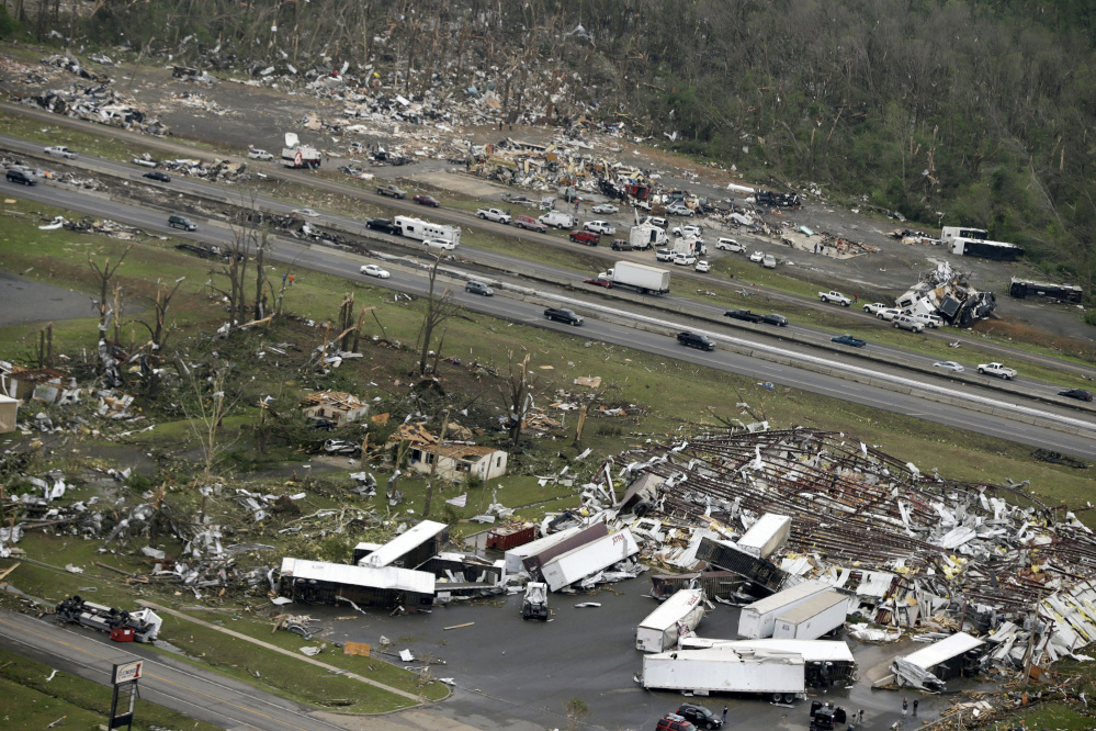 Traffic passes on Interstate 40 between destroyed businesses in Mayflower, Ark., on Monday after a tornado struck the town late Sunday.