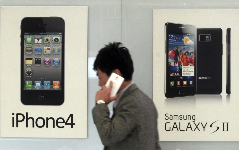 A man walks past banners advertising smartphones by Samsung and Apple at a mobile phone shop in Seoul, South Korea, in this 2013 file photo.