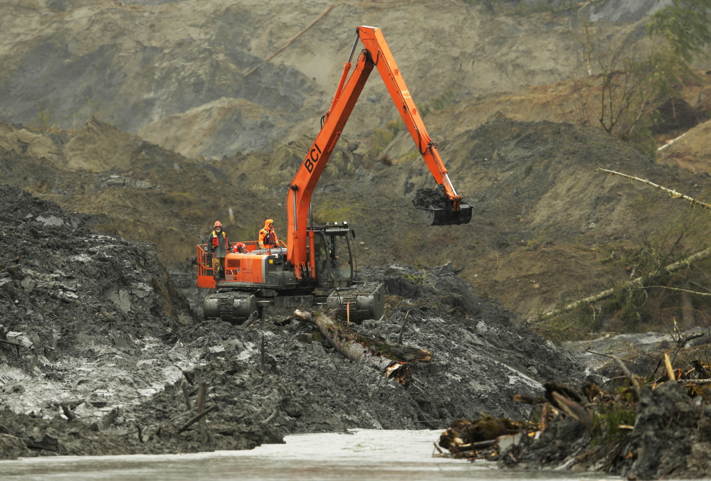 An excavator capable of floating on water is used to search through mud and debris that hit the community of Oso, Wash., earlier this month.