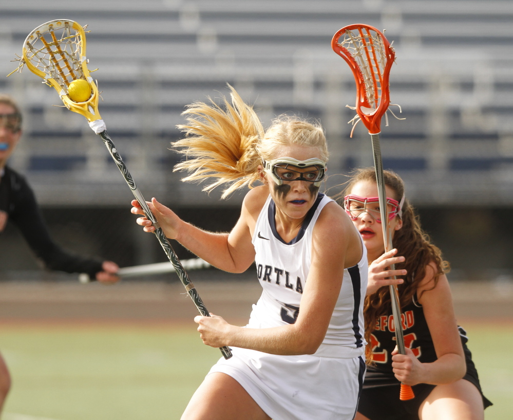 Hallie Allex of Portland works the ball down the field Tuesday while pursued by Rebekah Guay of Biddeford during Portland's 9-8 victory at Fitzpatrick Stadium.