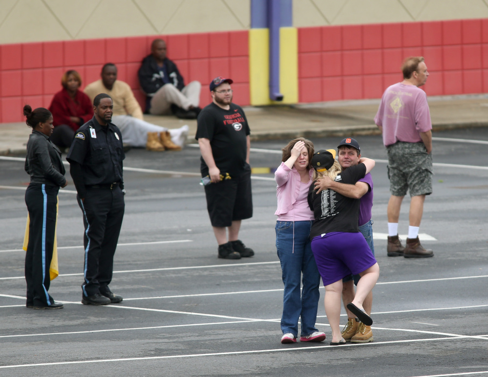 A FedEx employee, facing, is consoled after an early morning shooting Tuesday in Kennesaw, Ga.