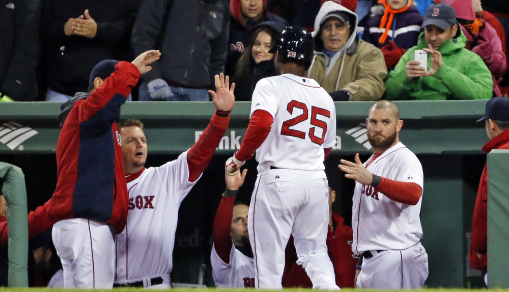 Jackie Bradley Jr. of the Boston Red Sox is welcomed to the dugout Tuesday night after scoring on Shane Victorino's double in the sixth inning of a 7-4 victory over Tampa Bay.