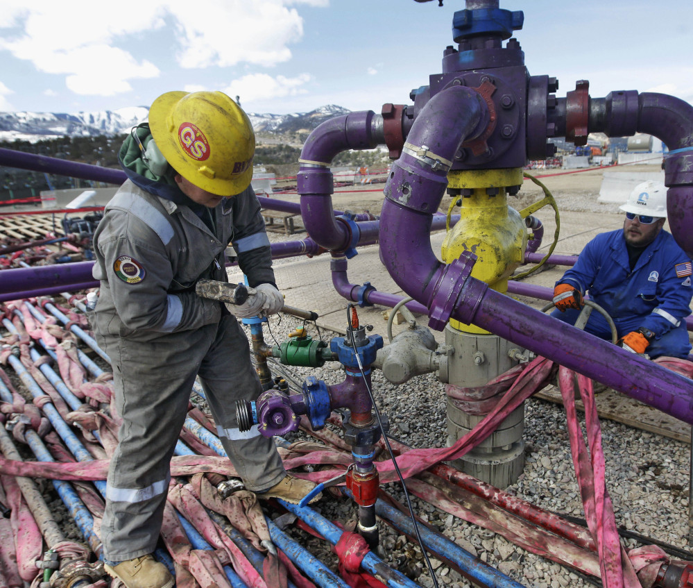 "Workers tend to a well head during a hydraulic fracturing operation at an Encana Oil & Gas Inc. site outside Rifle, in western Colorado. The ""fracking"" technique has allowed drillers to tap natural gas in formations once thought to be out of reach."