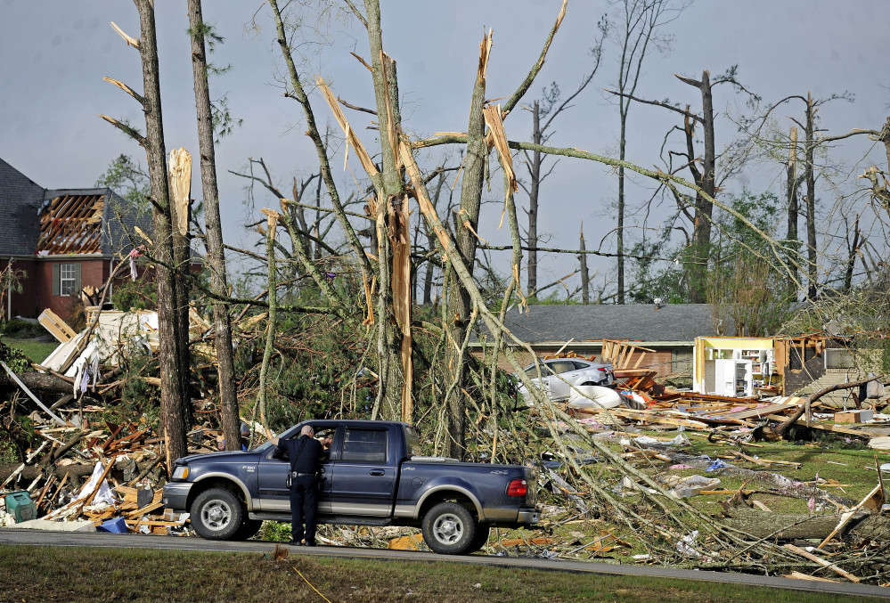 A police officer directs traffic in front of damaged homes Tuesday in Tupelo, Miss.