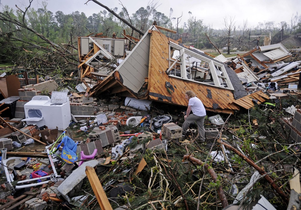Kevin Barnes searches the remains of his home Tuesday in Tupelo, Miss.