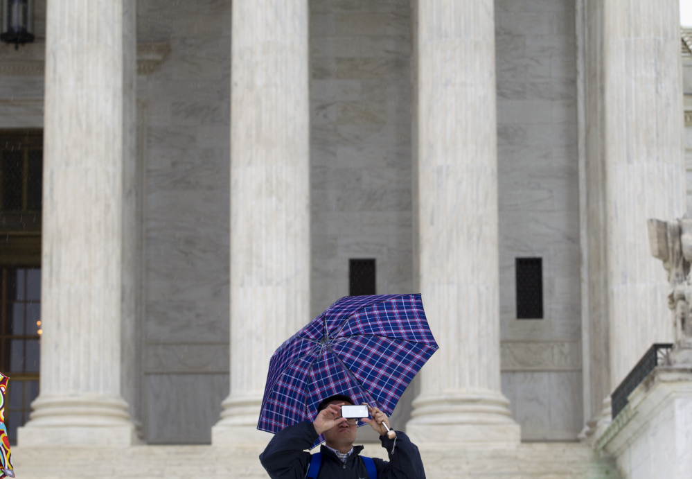 A man takes a picture Tuesday outside the U.S. Supreme Court, where justices were confronting the question of whether police need a warrant to search the cellphone of an arrested suspect.