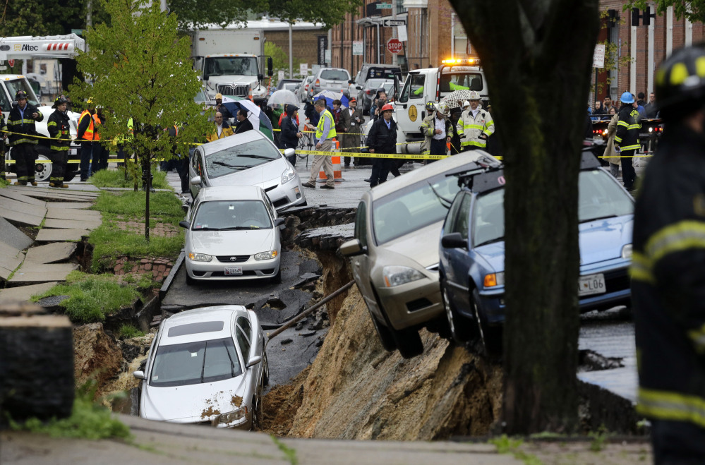 Cars sit on the edge of a sinkhole in Baltimore on Wednesday as heavy rain moves through the region.