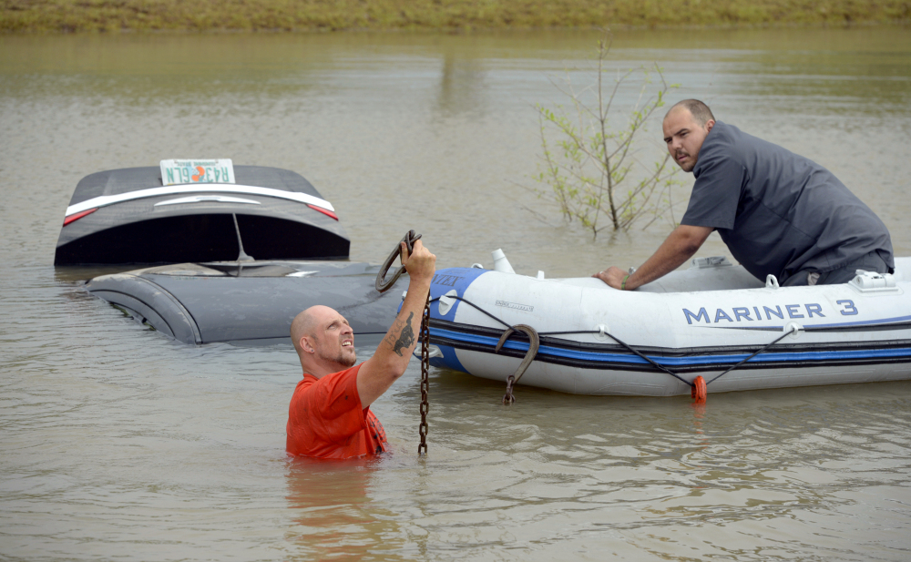 Michael Harrell, left, of J&J Towing holds up a tow cable before attaching it to a flooded car that was swept off Fairfield Avenue by torrential rains and deposited in a ditch as fellow employee Charles Thomas assists from an inflatable boat in Pensacola, Fla., on Wednesday.