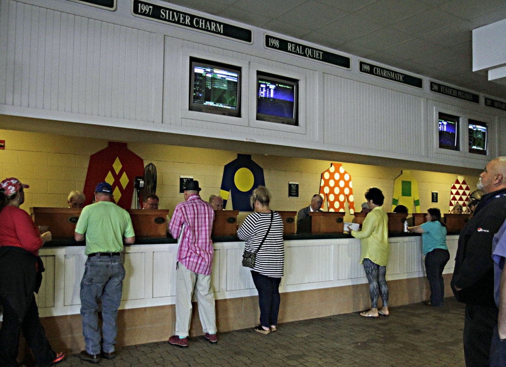 Horse racing patrons place wagers on races at Churchill Downs in Louisville, Ky., on Wednesday. Churchill Downs is taking a bigger cut of the money bettors place on its races.