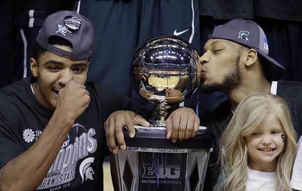 Lacey Holsworth, at right, stands with Michigan State's Gary Harris, left, and Adreian Payne as they pose with a championship trophy in March. Lacey and Payne became friends when he met her in a hospital, and she became an inspiration for the Spartans. Lacey, who was battling cancer, died Tuesday.