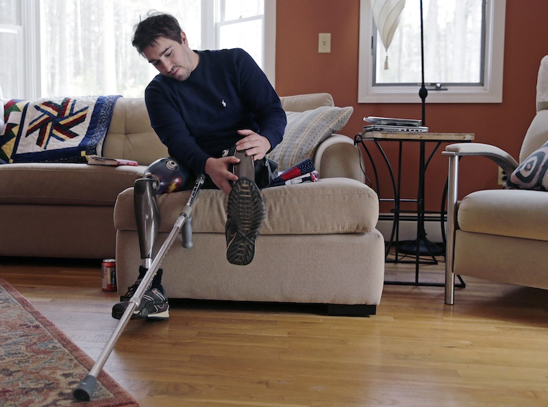 In this Friday, March 14, 2014 photo, Jeff Bauman adjusts one of his prosthetic legs at his home in Carlisle, Mass. Bauman, who lost both of his legs in the Boston Marathon bombings, helped identify one of the two brothers accused of setting off the explosions.
