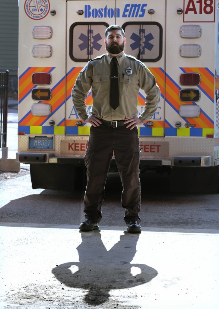 In this Thursday, March 20, 2014 photo, Boston Emergency Medical Services EMT Paul Mitchell stands next to an ambulance at his station in the Hyde Park neighborhood of Boston.