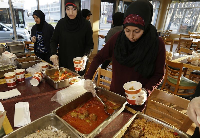 Volunteers Zahraa Debaja, center, and Zeinab Makki, right, prepare meals from food provided by the Yasmeen Bakery in Dearborn, Mich., Friday, April 25, 2014. The reach of one of the nation's few charitable organizations exclusively providing halal food to the poor could be greatly expanded under the new federal provision.