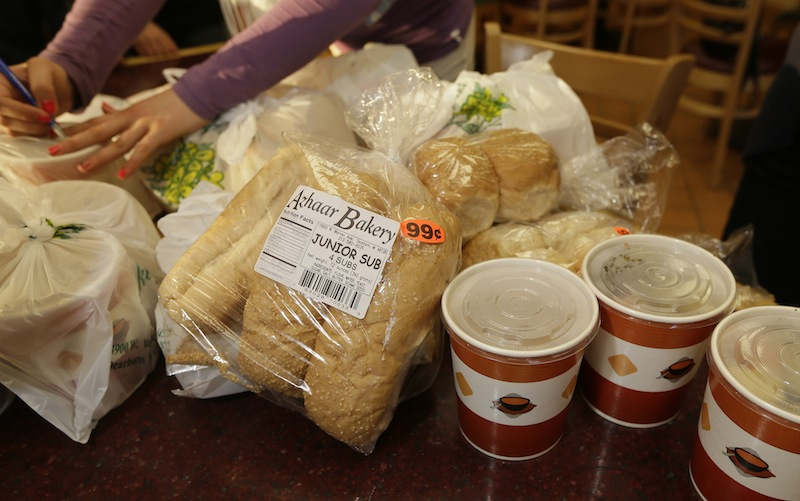 A volunteer labels food provided by the Yasmeen Bakery in Dearborn, Mich., Friday, April 25, 2014. The reach of one of the nation's few charitable organizations exclusively providing halal food to the poor could be greatly expanded under the new federal provision.