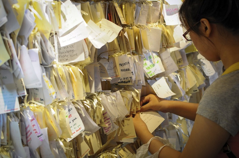 A woman ties a message card for passengers onboard the missing Malaysia Airlines Flight 370 at a shopping mall in Petaling Jaya, near Kuala Lumpur, Malaysia, Thursday, April 10, 2014.
