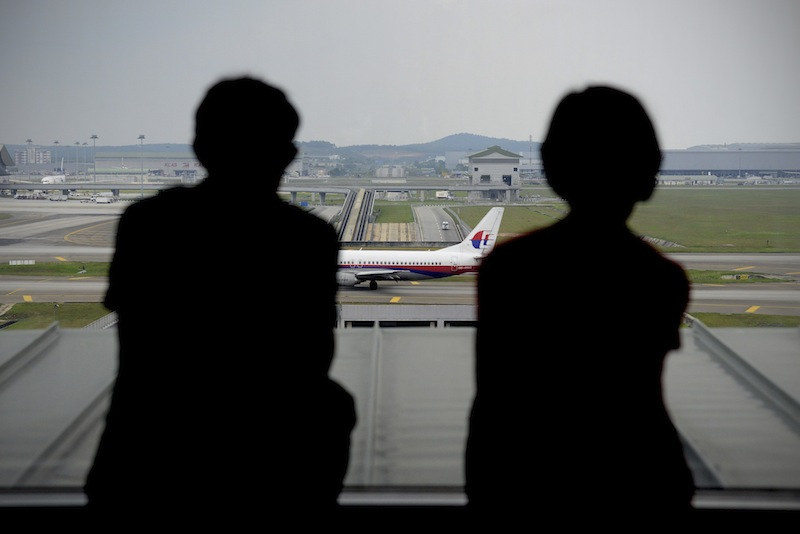 A couple is silhouetted as they watch a Malaysia Airlines plane on the tarmac from the viewing gallery at Kuala Lumpur International Airport in Sepang, Malaysia, Thursday, April 10, 2014. With hopes high that search crews are zeroing in on the missing Malaysian jetliner's crash site, ships and planes hunting for the aircraft intensified their search efforts on Thursday after equipment picked up sounds consistent with a plane's black box in the deep waters of the Indian Ocean.