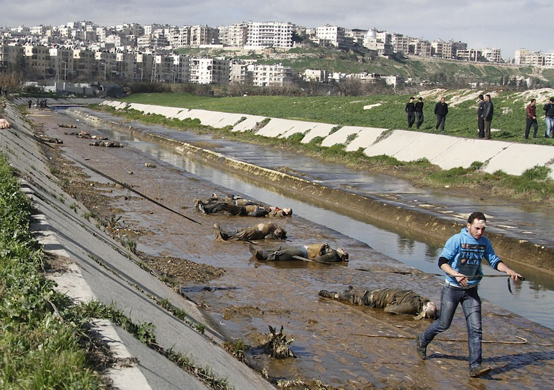 In this Jan. 29, 2013, file photo, a man walks past dead bodies in front of a river in the neighborhood of Bustan al-Qasr in Aleppo, Syria. The Britain-based Syrian Observatory for Human Rights said Tuesday that it has documented 150,344 deaths in the conflict that started in March 2011. The figure includes civilians, rebels, and members of the Syrian military. It also includes militiamen, fighting alongside President Bashar Assad's forces and foreign fighters battling for Assad's ouster on the rebels' side. (AP Photo/Abdullah al-Yassin, File)