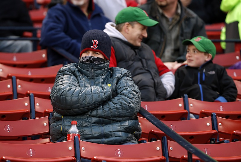 A fan is bundled up against the cold at Fenway Park on Tuesday. Wednesday night's game against the Tampa Bay Rays was rescheduled for Thursday afternoon due to inclement weather.
