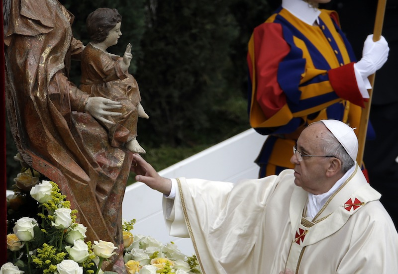 Pope Francis touches a statue of the Virgin Mary as he leads a solemn ceremony in St. Peter's Square at the Vatican on Sunday.