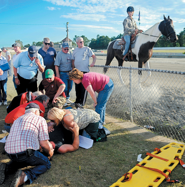 People attend to the injured who were struck by the racing gate at the start of the 13th race at the WIndsor Fair in this September 2010 photo. The gate, towed by a vehicle, hit five people watching the race.