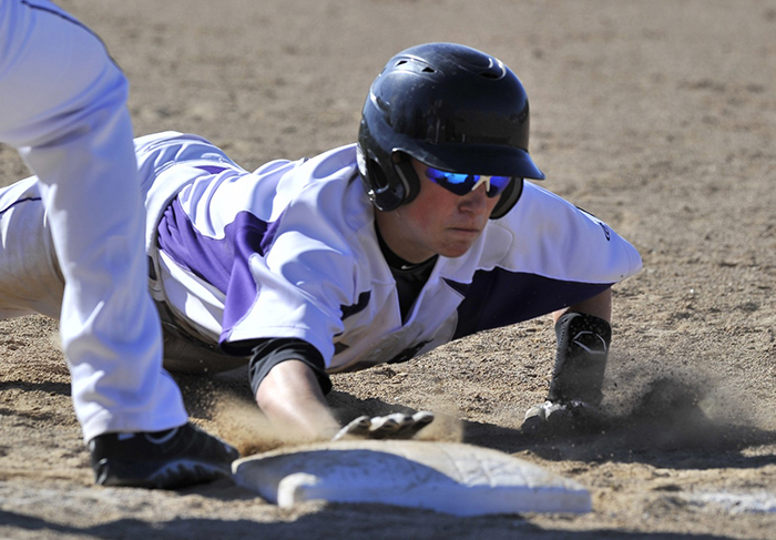 In this May 7, 2013, photo, Deering's Nick Bevilaqua dives back to first in a pickoff attempt as Biddeford hosts Deering in high school baseball action. In an effort to cut down on pitchers deceiving runners on pickoff moves, a new rule this year requires a pitcher to keep his feet together when starting a delivery, rather than having one foot in front or to the side.