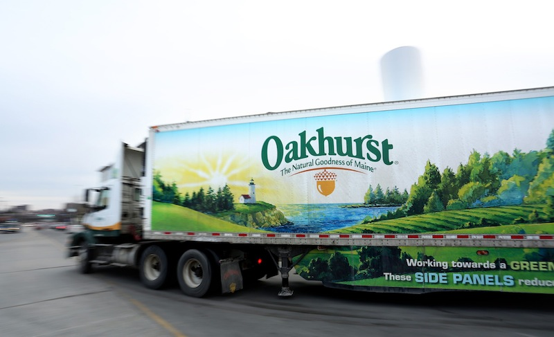 In this January 2014 file photo, an Oakhurst Dairy truck leaves the company headquarters on Forest Avenue in Portland. Two former and one current Oakhurst delivery drivers have filed a class-action lawsui claiming that the Portland-based company has failed for years to pay them overtime compensation in violation of state and federal wage laws.
