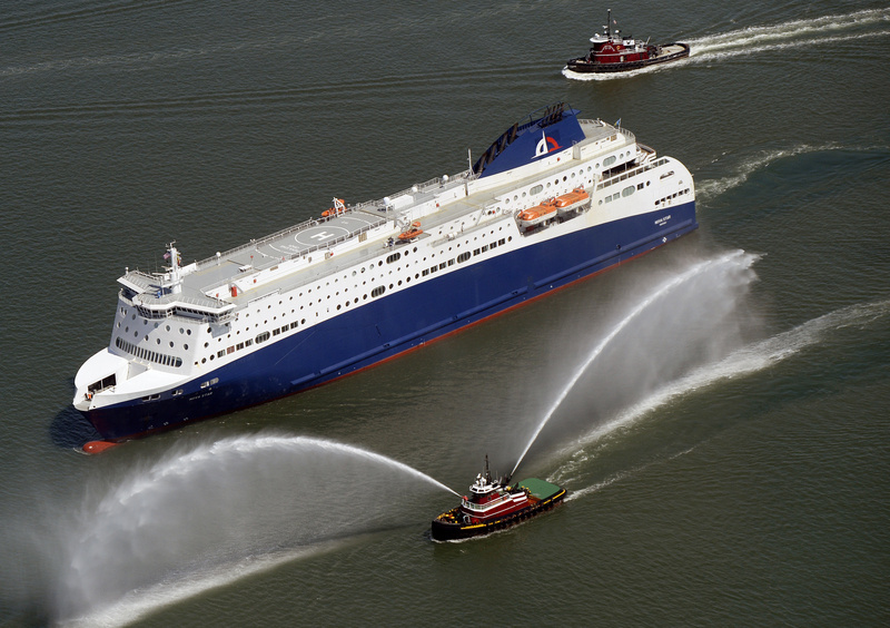 A tugboat gushes dual fountains of water in greeting as the Nova Star ferry cruises into Portland Harbor on April 17, 2014.