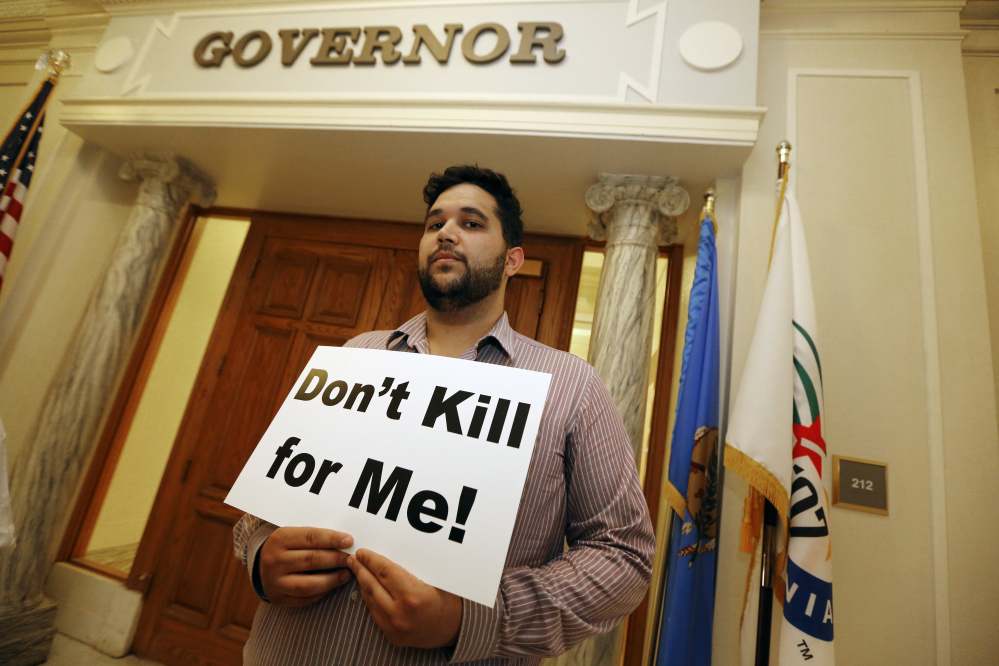 Hossein Dabiri with Oklahoma Coalition Against the Death Penalty holds a sign protesting the death penalty at the State Capitol in Oklahoma City on Tuesday. Oklahoma prison officials halted the execution of an inmate after the delivery of a new three-drug combination on Tuesday failed to go as planned.
